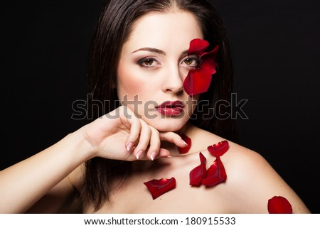 Fashion portrait of woman with rose petals on her face