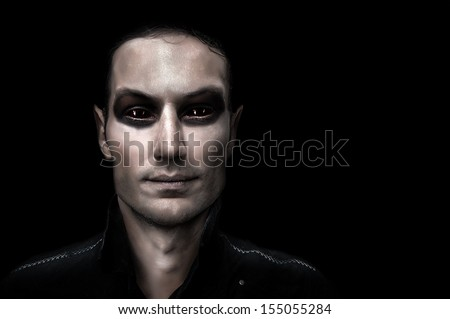 Fashion portrait of young adult man vampire on black background