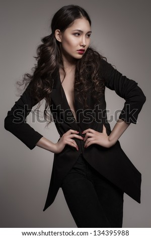 fashion portrait of young asian woman on dark gradient background - stock photo