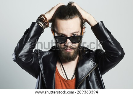 fashion Portrait of young bearded man in leather jacket. Hipster in sunglasses.haircare - stock photo