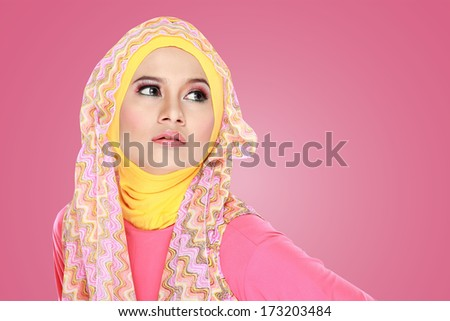 Fashion portrait of young beautiful asian muslim woman with pink costume wearing hijab - stock photo