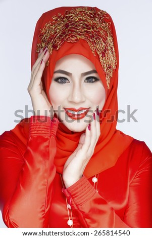 Fashion portrait of young beautiful asian muslim woman with red costume wearing hijab - stock photo