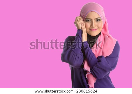 Fashion portrait of young beautiful asian muslim woman with wearing hijab with pink background - stock photo