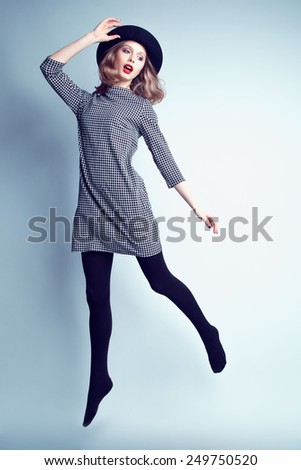 Fashion portrait of young beautiful female model  in casual trendy dress and hat jumping and flying. - stock photo