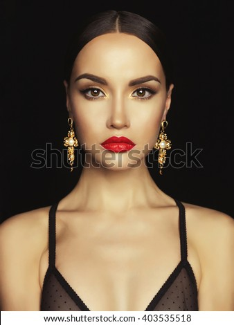 Fashion portrait of young beautiful lady with earrings on black background - stock photo