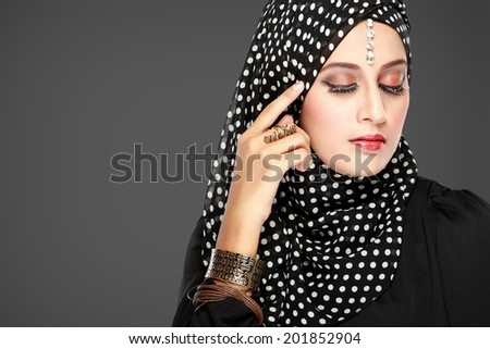 Fashion portrait of young beautiful muslim woman with black scarf isolated on grey background - stock photo