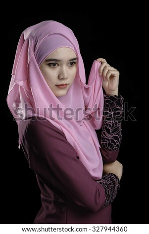 Fashion portrait of young beautiful muslim woman with maroon costume wearing pink color hijab isolated on black background - stock photo