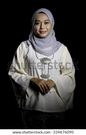 Fashion portrait of young beautiful muslim woman with modern kebaya with hijab isolated on black background - stock photo