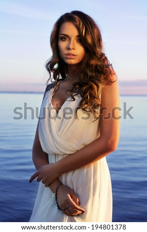 fashion portrait of young beautiful sexy lady in white dress with decollete posing against blue sea and sky at sunset - stock photo