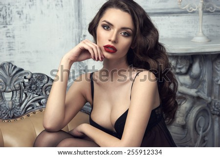 Fashion portrait of young beautiful sexy woman with long wavy hair. Pretty girl sitting in black bra or lingerie in luxury interior and looking at you. - stock photo