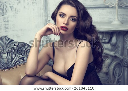 Fashion portrait of young beautiful sexy woman with long wavy hair. Pretty girl sitting in black bra or lingerie in luxury interior. Fashion style toned colors portrait