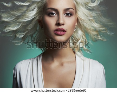 Fashion portrait of young beautiful woman. Flying hair Blond girl. Curly hairstyle.green background - stock photo