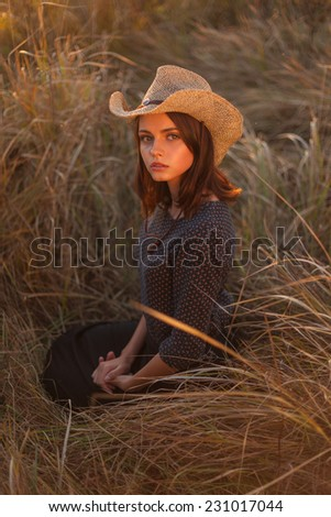 Fashion portrait of young beautiful woman in hat, sitting in the high autumnal grass. - stock photo