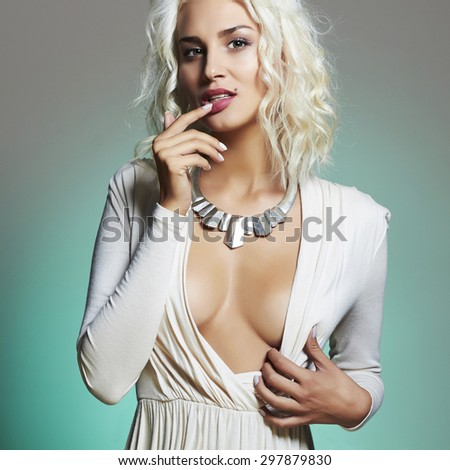 Fashion portrait of young beautiful woman. Sexy decollete blonde. Blond girl. Curly hairstyle.green background - stock photo