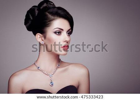 Fashion portrait of young beautiful woman with jewelry and elegant hairstyle. Brunette girl. Perfect make-up. Beauty style woman with diamond accessories