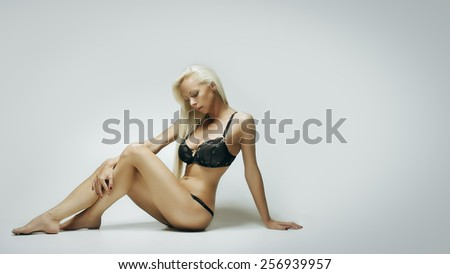 Fashion portrait of young blond woman in lingerie on white