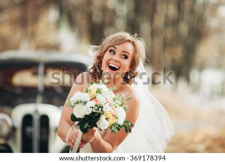 Fashion portrait of young bride with white dress with bouquet near retro car in autumn - stock photo