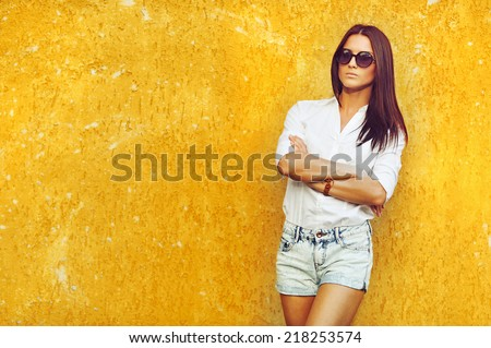 Fashion portrait of young brunette model posing by the wall - stock photo