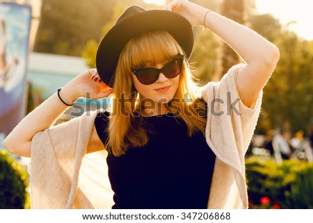 fashion portrait of young brunette woman in a black dress and black sunglasses with a hat on his head against the setting sun,grey sweater and leather bag. Cold season.Red lips. Warm clothes. - stock photo