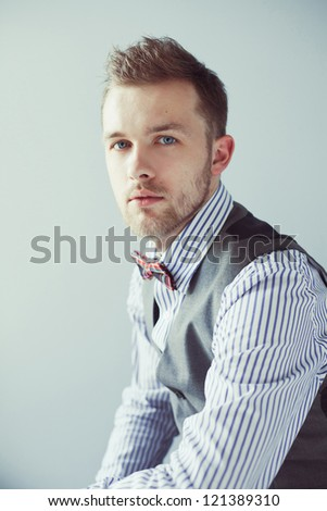 Fashion portrait of young business man in suit with bow tie - stock photo