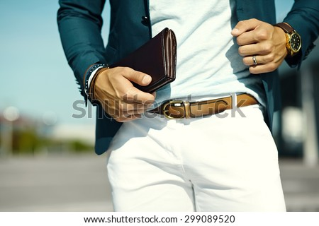 Fashion portrait of young businessman handsome  model man in casual cloth suit with accessories on hands - stock photo