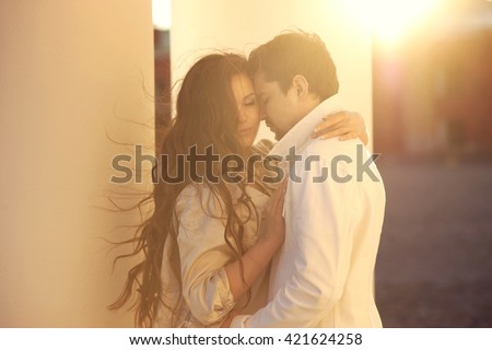 Fashion portrait of young couple in love posing at street. Beautiful girl and handsome boy hugging outdoors - stock photo