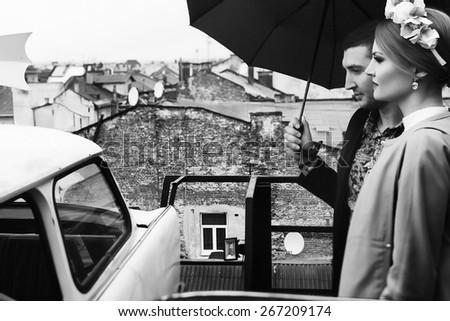 fashion portrait of young couple under the umbrella - stock photo