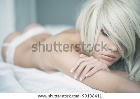 Fashion portrait of young elegant woman in bed - stock photo