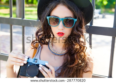 Fashion portrait of young girl make picture and look at camera in summer stylish outfit on sunset.Natural make-up,fashion summer accessories,perfect nails,red lips,bright colors,fashion sunglasses - stock photo