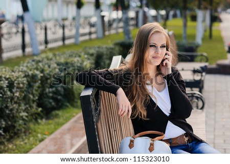 Fashion portrait of young gorgeous blond outdoors. Talking on cell phone - stock photo