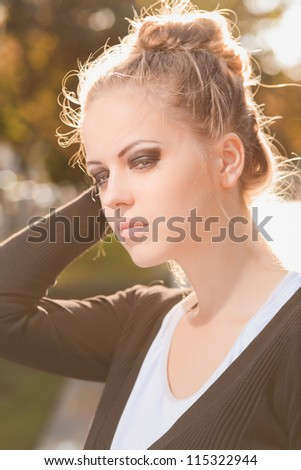 Fashion portrait of young gorgeous blond outdoors. With glare of the sun