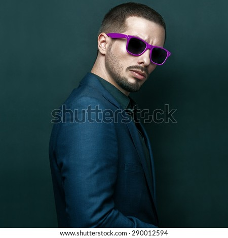 Fashion portrait of young handsome brutal bearded man in dark blue suit and purple sunglasses. - stock photo
