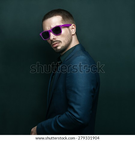 Fashion portrait of young handsome brutal bearded man in suit and sunglasses. - stock photo