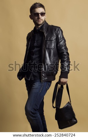 Fashion portrait of young handsome man model in leather jacket holding leather bag, wearing trendy sunglasses and poses over beige background. Close up. Copy-space. - stock photo