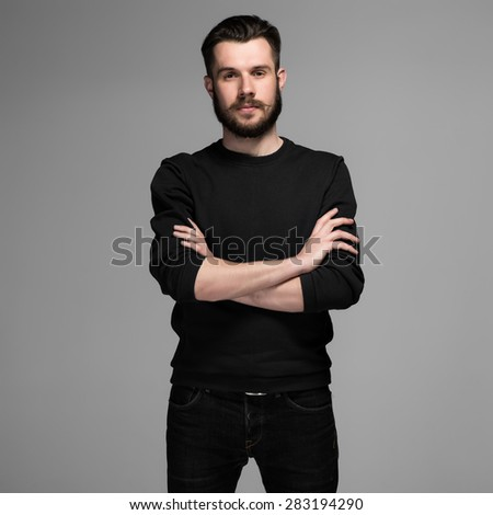 Fashion portrait of young man in black  poses over gray background. hands folded on his chest - stock photo