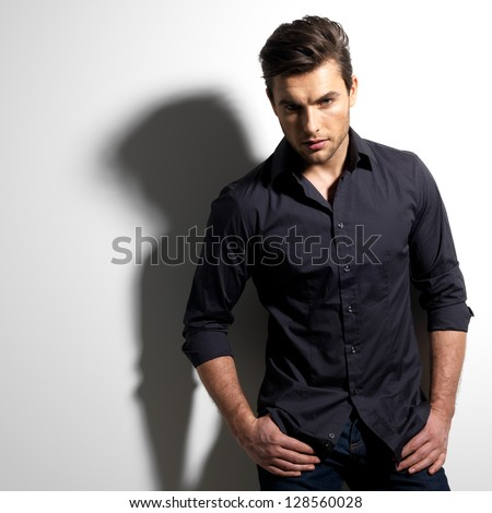 Fashion portrait of young man in black shirt poses over wall with contrast shadows - stock photo