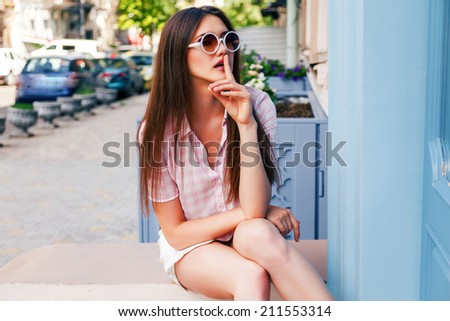 Fashion portrait of young model with long straight brunette hair posing at the street wearing hipster round sunglasses and plaid shirt. - stock photo