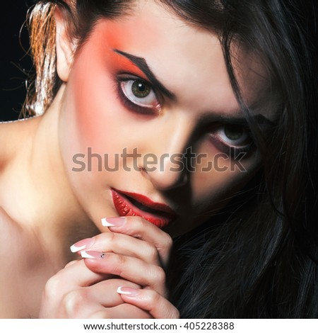 Fashion portrait of young passionate model. Woman with makeup in red colors. Studio shot.