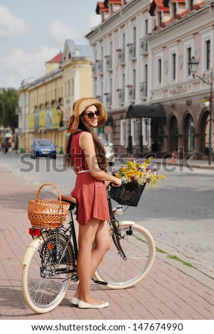 fashion portrait of young pretty brunette with bicycle - stock photo