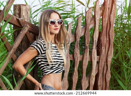 Fashion portrait of young pretty cute blonde girl. Beautiful woman posing on green background in summer day, outdoors - stock photo