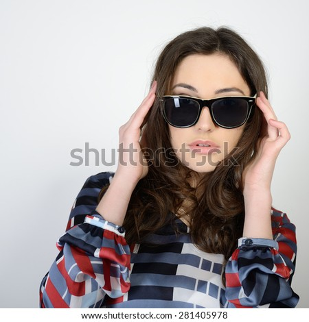 Fashion portrait of young pretty woman posing in sunglasses