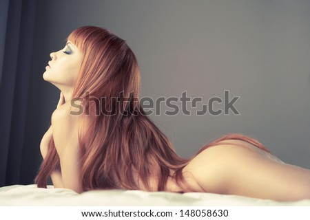 Fashion portrait of young sensual woman in bed - stock photo