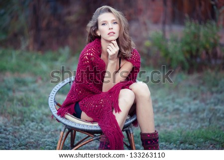 Fashion portrait of young sensual woman in garden  sitting in the chair - stock photo
