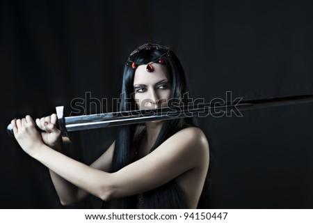 Fashion portrait of young sexy brunette woman with sword - stock photo