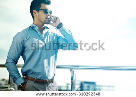 Fashion portrait of young sexy businessman handsome  model man in casual cloth suit in sunglasses in the street speaking on his phone - stock photo