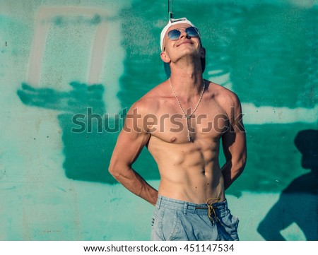 Fashion portrait of young sexy handsome muscled model man in casual cloth in sunglasses in the street showing his abdominal muscles - stock photo