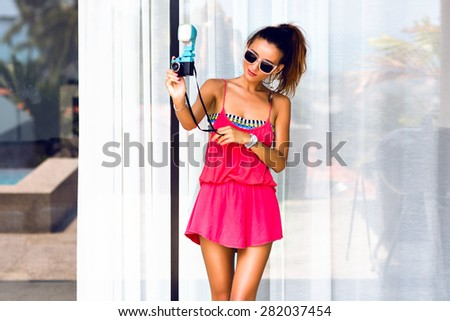 Fashion portrait of young sexy hipster photographer  woman, wearing bright summer stylish outfit, making photos on vintage camera. Having fun alone. - stock photo