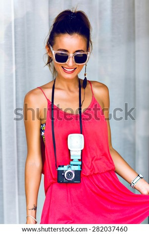 Fashion portrait of young sexy hipster photographer  woman, wearing bright summer stylish outfit, making photos on vintage camera, have ponytail and big sunglasses. - stock photo