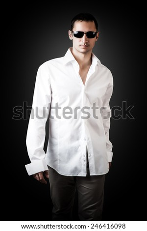 Fashion portrait of young sexy man wearing white luxury shirt and sunglasses walking on black background - stock photo