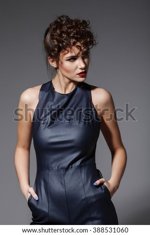 Fashion portrait of young sexy woman with hairstyle posing on grey background